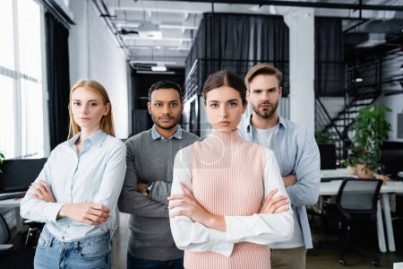 Multicultural businesspeople with crossed arms looking at camera in office