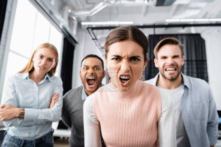 Photo pour Femme d'affaires agressive regardant la caméra près de collègues multiethniques sur fond flou - image libre de droit