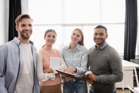Photo pour Hommes d'affaires multiethniques avec dossier papier et tablette numérique souriant à la caméra dans le bureau - image libre de droit