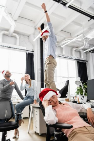 Photo for Businesswoman in santa hat sleeping near cheerful multiethnic colleagues on blurred background in office - Royalty Free Image
