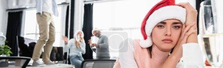 Photo pour Femme d'affaires fatiguée en santa chapeau regardant la caméra près de verre de champagne et collègues sur fond flou, bannière - image libre de droit