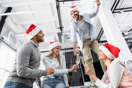 Multiethnic businesspeople with glasses of champagne and santa hat celebrating Christmas in office