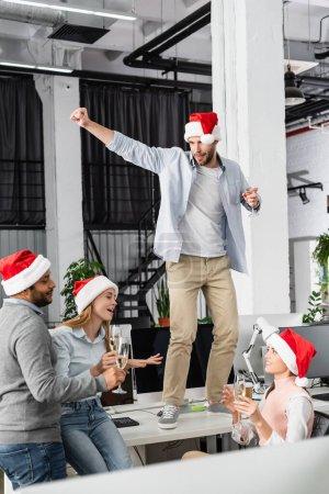 Empresarios multiétnicos sosteniendo copas de champán mientras celebran el año nuevo en el cargo