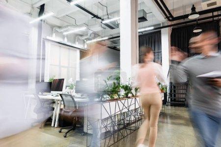 Motion blur of businesspeople walking in modern office