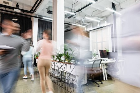 Motion blur of young businesspeople walking in modern office