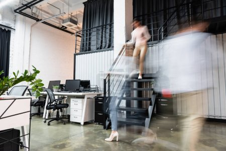 Motion blur of businesswomen and businessman walking in modern office near computers