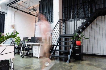 Motion blur of businesswomen walking near computers in office
