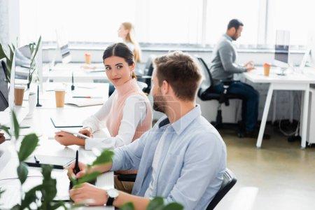Photo pour Femme d'affaires regardant collègue tout en utilisant une tablette numérique dans le bureau - image libre de droit