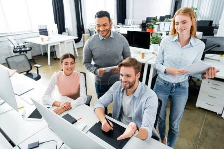 Photo for Smiling multicultural businesspeople using graphics tablet and computer in office - Royalty Free Image