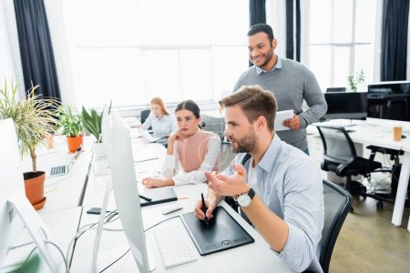 Businessman using graphics tablet and computer near multicultural colleagues in office