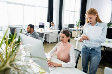 Businesswoman with papers looking at wristwatch near colleague using computer in office