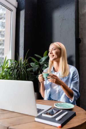 happy freelancer holding cup of coffee near laptop on blurred foreground