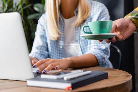 Photo pour Vue recadrée du serveur tenant tasse de café près freelance dactylographier sur ordinateur portable dans le café - image libre de droit