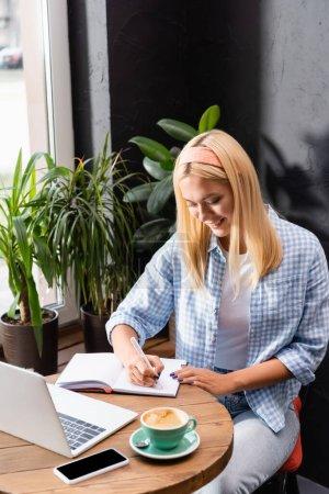 Photo pour Écriture pigiste souriante dans un carnet près d'un ordinateur portable, smartphone avec écran vierge et tasse de café - image libre de droit