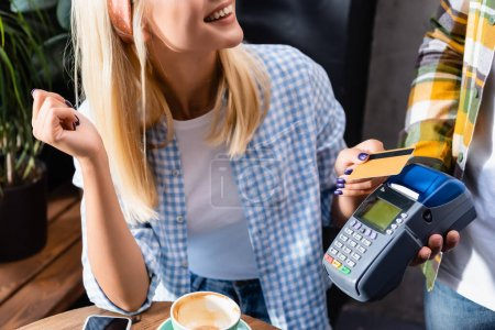 cropped view of smiling woman holding credit card near waiter with payment terminal