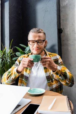 Photo pour Plaisir freelance profiter saveur de café tout en tenant tasse près de l'ordinateur portable et smartphone avec écran blanc - image libre de droit