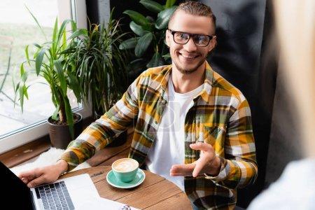Photo pour Joyeux pigiste dans les lunettes et chemise à carreaux pointant avec la main près de tasse de café et ordinateur portable dans le café - image libre de droit