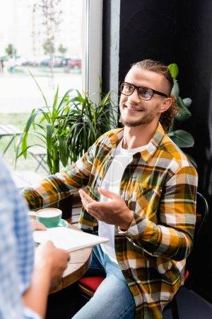 Photo pour Jeune homme souriant dans les lunettes pointant avec le doigt près du serveur sur le premier plan flou - image libre de droit