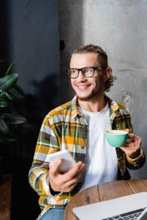 feliz freelancer en camisa a cuadros y anteojos mirando hacia otro lado mientras sostiene el teléfono inteligente y la taza de café en primer plano borroso