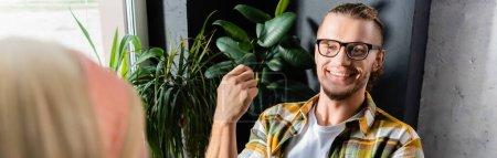 Photo pour Joyeux jeune homme en chemise à carreaux et lunettes souriant au café, bannière - image libre de droit
