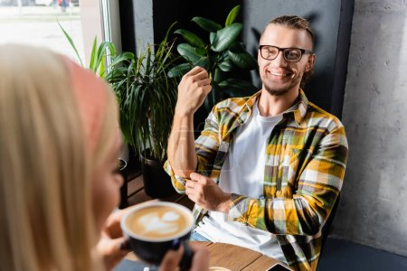 Photo pour Jeune homme souriant aux lunettes regardant une femme tenant une tasse de café au premier plan flou - image libre de droit