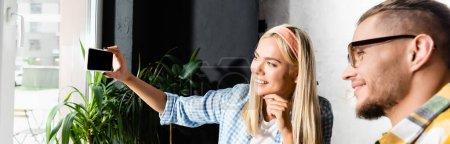 fröhliche blonde Frau macht Selfie auf Handy mit Freundin im verschwommenen Vordergrund, Banner