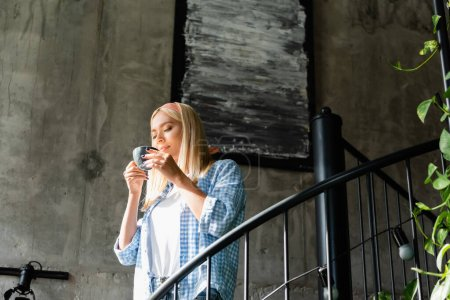 young blonde woman in plaid shirt enjoying flavor of coffee while holding cup on stairway in cafe