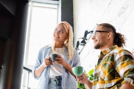 junges stylisches Paar schaut weg, während es mit Kaffeetassen auf der Treppe im Café steht