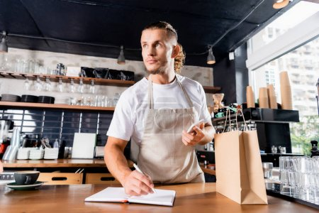 young barista holding smartphone while writing in notebook near paper bag on bar counter