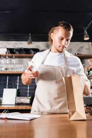 handsome barista in apron looking into paper bag while holding smartphone near notebook on blurred foreground
