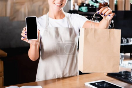 cropped view of barista holding paper bag and showing smartphone with blank screen, blurred background