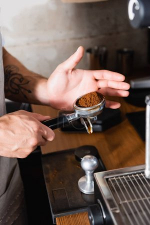 Photo for Cropped view of tattooed barista holding portafilter with roasted ground coffee - Royalty Free Image