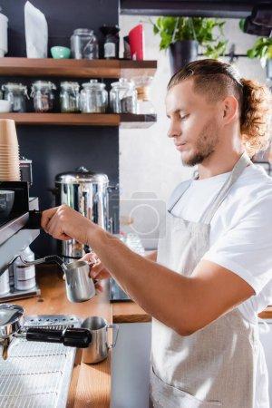 Photo pour Jeune barista dans tablier tenant tasse de lait métallique près de la machine à café vapeur - image libre de droit