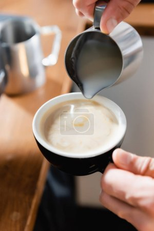 partial view of barista pouring milk into cup with coffee