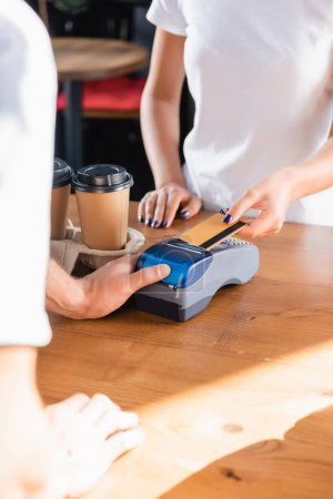Photo for Cropped view of woman paying with credit card through payment terminal near barista on blurred foreground in cafe - Royalty Free Image