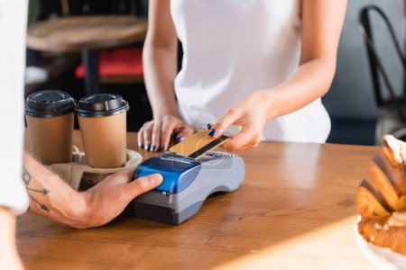 partial view of woman holding credit card near barista with payment terminal on blurred foreground