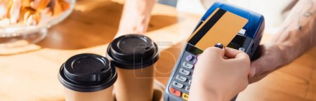 cropped view of woman paying with credit card through terminal near takeaway coffee in cafe, banner