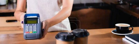 Photo for Partial view of barista holding payment terminal near coffee to go on blurred foreground, banner - Royalty Free Image