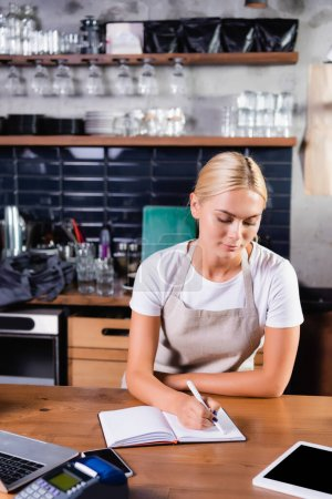 young blonde barista writing in notebook near gadgets and payment terminal on blurred foreground