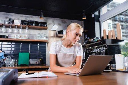Photo pour Jeune blonde barista à l'aide d'un ordinateur portable près d'un ordinateur portable sur le comptoir du bar, au premier plan flou - image libre de droit