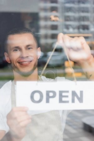 happy barista hanging card with open lettering on cafe entrance door