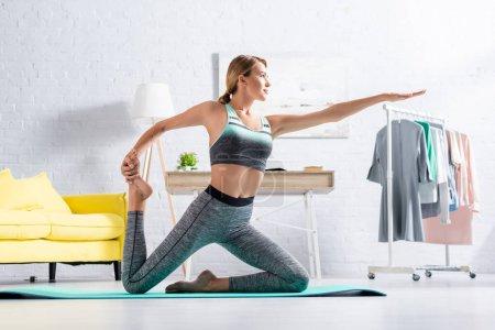 Foto de Ajuste la deportista que estira mientras que practica yoga en la estera en el país - Imagen libre de derechos