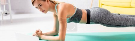 Sportswoman looking at laptop on blurred foreground while standing in plank, banner