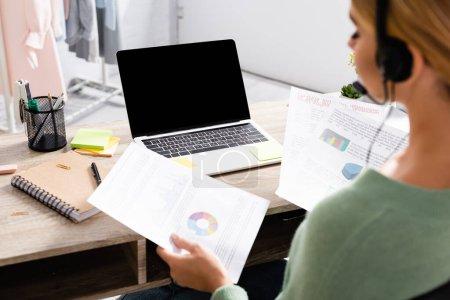 Photo pour Ordinateur portable avec écran blanc sur la table près freelance dans un casque tenant des papiers avec des graphiques sur le premier plan flou - image libre de droit