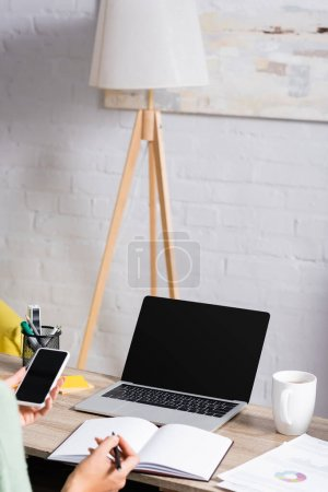 Photo for Laptop with blank screen near papers and cup on table near freelancer holding smartphone and pen on blurred foreground - Royalty Free Image
