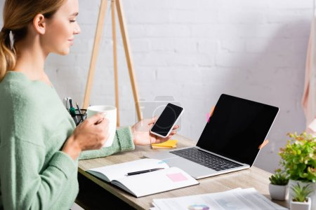 Photo for Laptop with blank screen on table near smiling freelancer holding smartphone and cup with papers on blurred foreground on table - Royalty Free Image