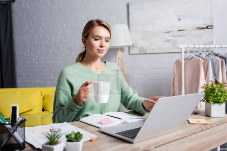 Photo for Freelancer with cup using laptop near notebook and documents on blurred foreground at home - Royalty Free Image