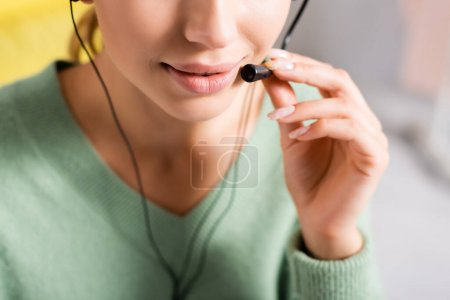 Cropped view of young woman using headset at home