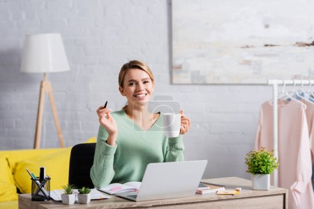 Cheerful freelancer holding cup and pen while working with papers and laptop on blurred foreground at home
