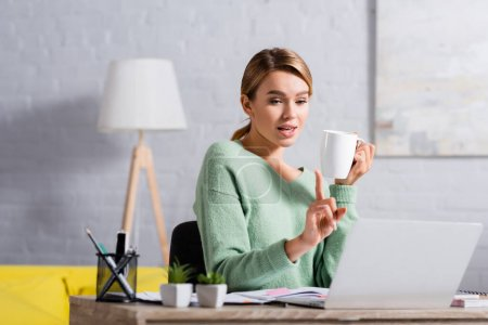 Photo for Freelancer with cup pointing with finger during video call on laptop on blurred foreground - Royalty Free Image